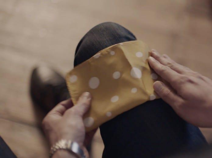 Um rapaz dobrando o lenço de bolso no seu joelho.