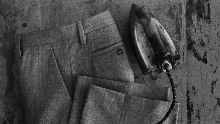 Freshly ironed dress pants next to an old iron.