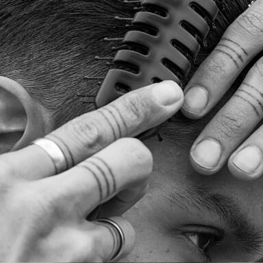 Um rapaz com tatuagens nos dedos, escovando o cabelo.