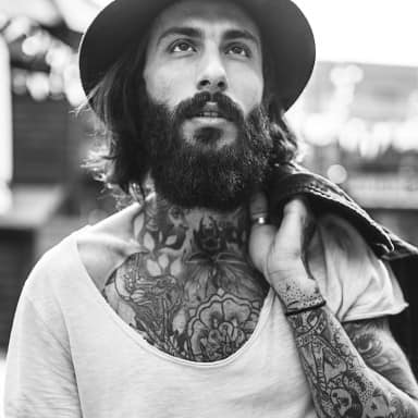 Um cara com barba cheia e tatuagens.