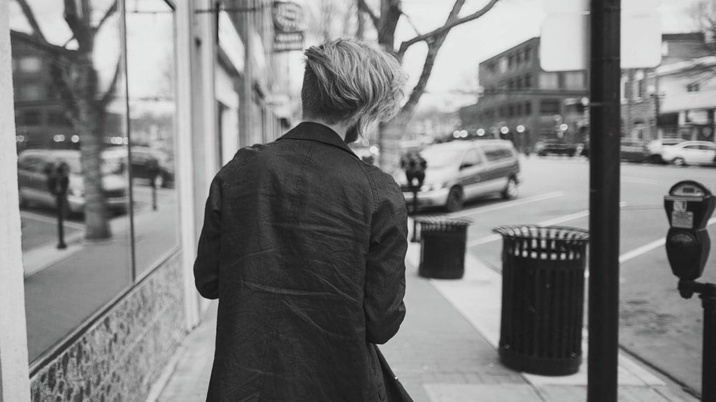 Um cara de cabelos longos andando numa rua da cidade.
