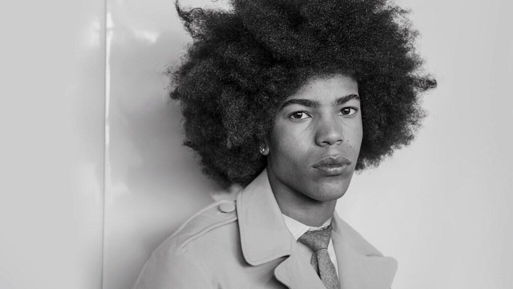 Um rapaz com cabelo afro usando um sobretudo.