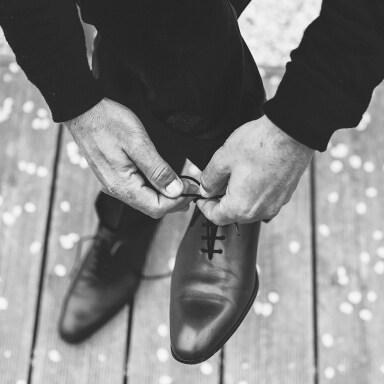 Um rapaz amarrando os cadarços nos seus sapatos Brogue.