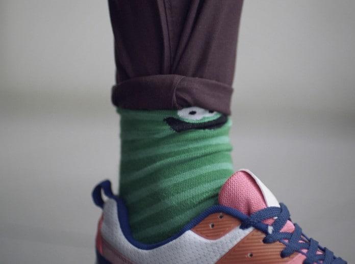 Um rapaz com meias e tênis coloridos, com a barra da calça dobrada.