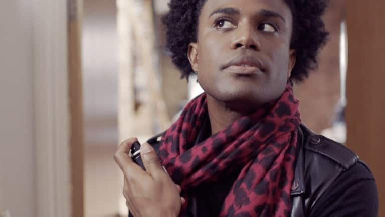 A man, in a scarf, spraying fragrance.