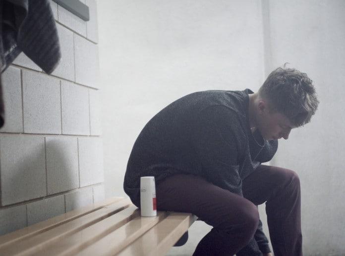 Um rapaz com roupa casual em um vestiário.
