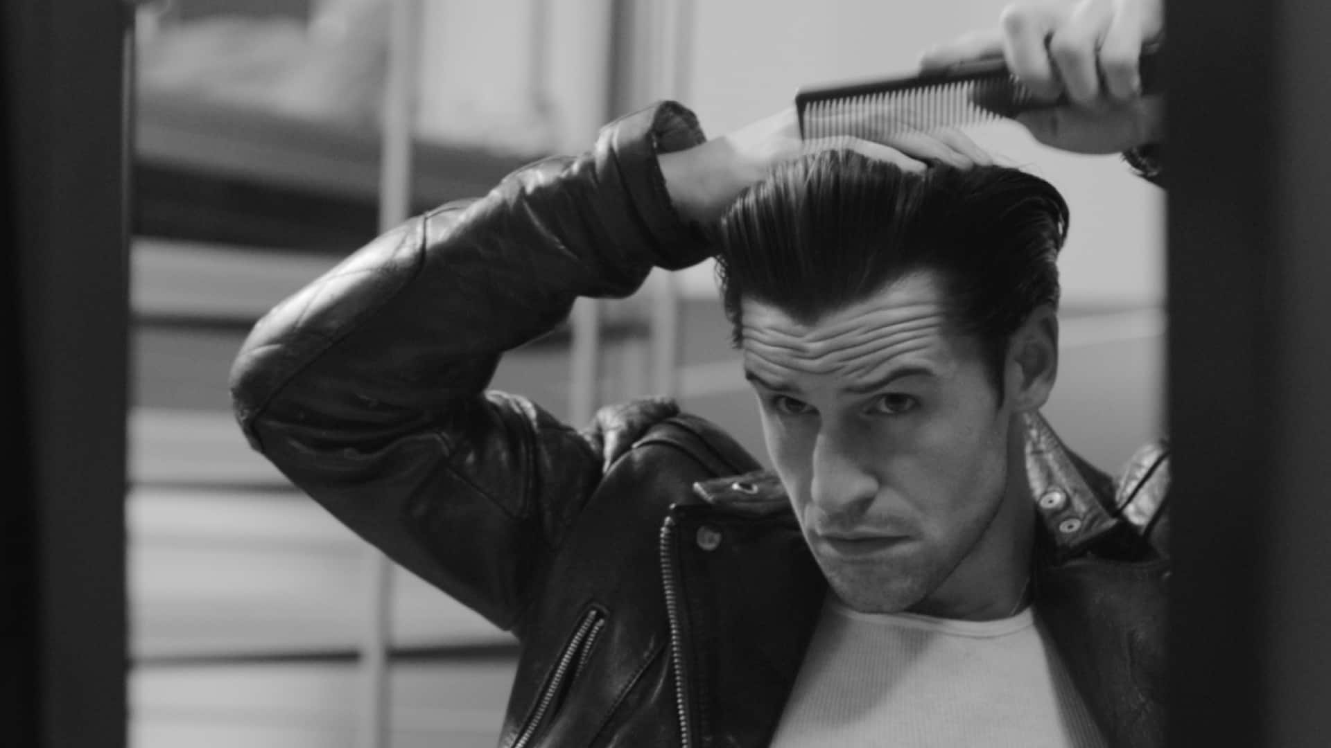 A guy brushing his hair in to a quiff.