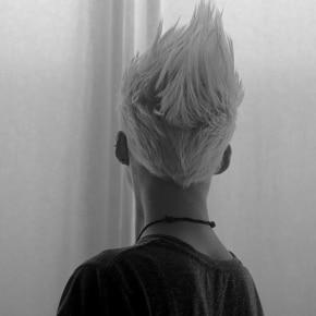 O cabelo moicano de uma garota loira visto de trás.
