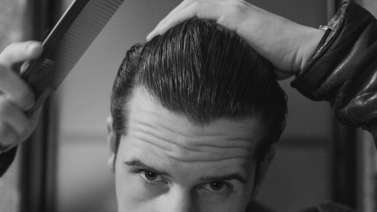 A guy with a pompadour, combing it.