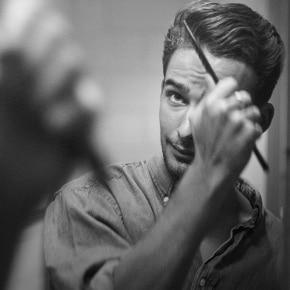 Um rapaz penteando seu topete no espelho.